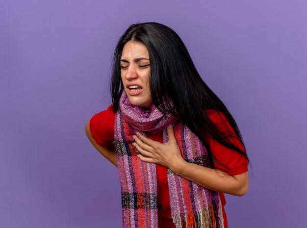 Pijnlijke jonge blanke ziek meisje dragen sjaal handen op de borst en op de rug met gesloten ogen zetten geïsoleerd op paarse muur met kopie ruimte