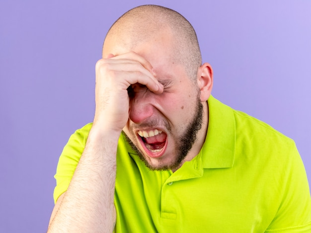 Pijnlijke jonge blanke zieke man legt hand op voorhoofd op paars