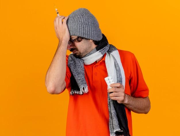 Pijnlijke jonge blanke zieke man met bril, muts en sjaal met spuit en pakje medische tabletten hand op het hoofd houden met gesloten ogen geïsoleerd op oranje muur met kopie ruimte