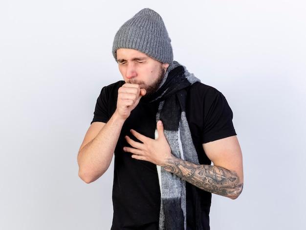 Pijnlijke jonge blanke zieke man met winter hoed en sjaal hoest en legt de hand op de borst op wit