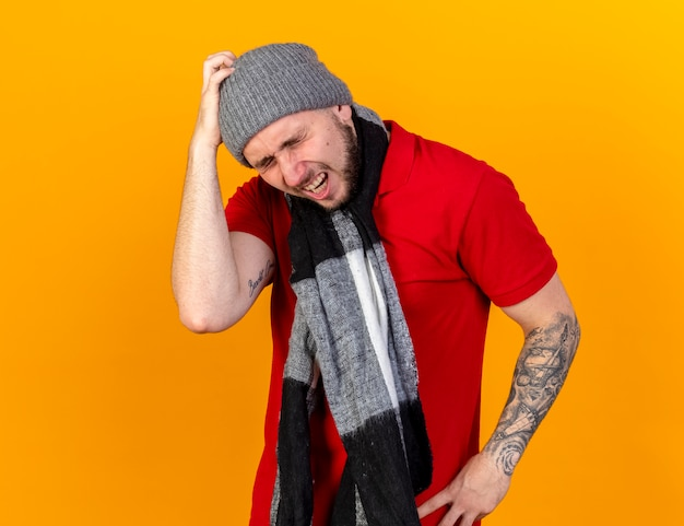 Pijnlijke jonge blanke zieke man met winter hoed en sjaal legt hand op het hoofd op oranje