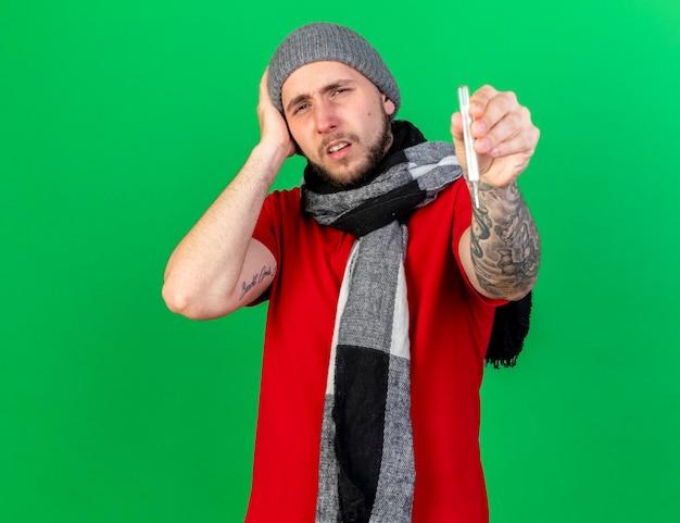 Pijnlijke jonge blanke zieke man met winter hoed en sjaal legt hand op het hoofd