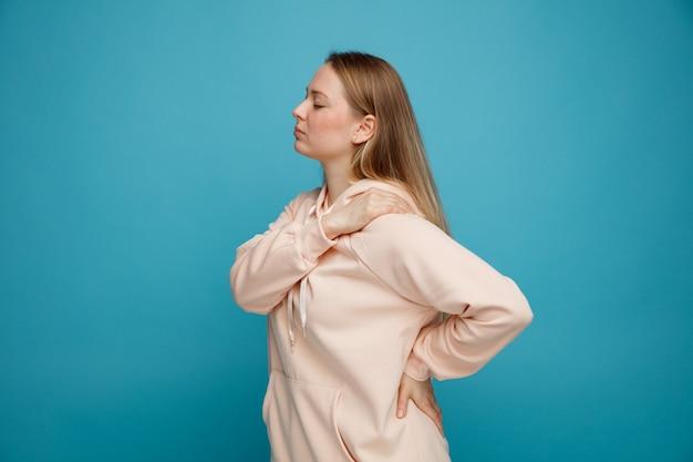 Pijnlijke jonge blonde vrouw die zich in profielmening bevindt die hand op taille en op schouder met gesloten ogen houdt
