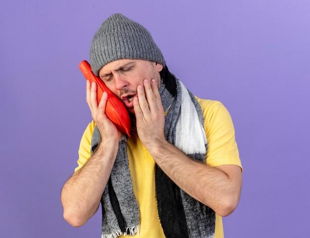 Pijnlijke jonge blonde ziek slavische man met muts en sjaal