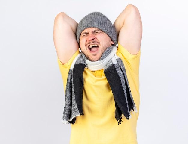 Pijnlijke jonge blonde zieke man met winter muts en sjaal houdt tegen met twee handen geïsoleerd op een witte muur