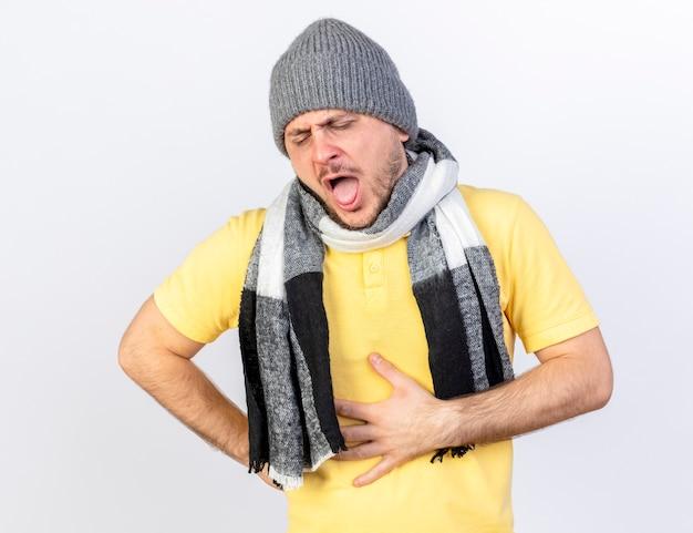 Pijnlijke jonge blonde zieke man met winter muts en sjaal legt hand op buik geïsoleerd op een witte muur