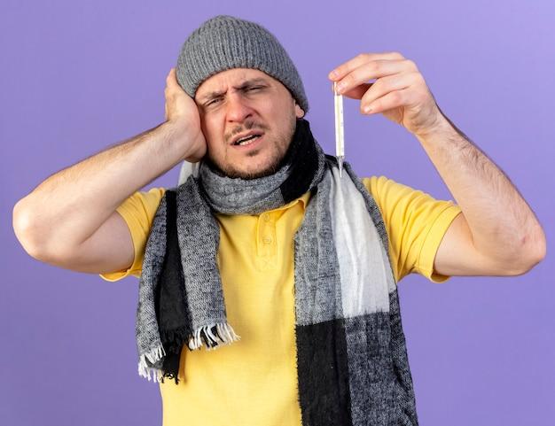 Pijnlijke jonge blonde zieke man met winter muts en sjaal legt hand op het hoofd houdt thermometer geïsoleerd op paarse muur