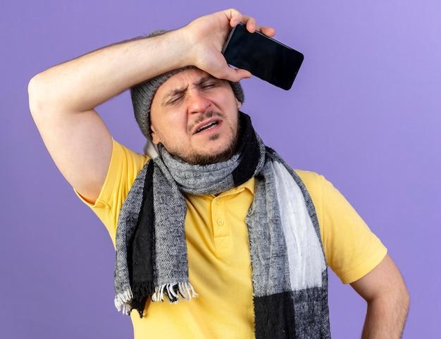 Pijnlijke jonge blonde zieke slavische man met winter hoed