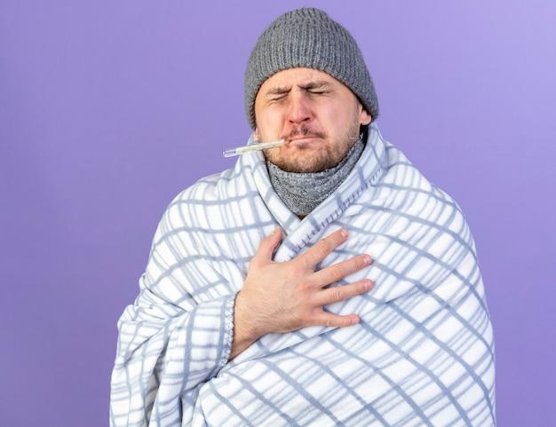 Pijnlijke jonge blonde zieke slavische man met winter muts en sjaal gewikkeld in plaid temperatuur meten met thermometer legt hand op borst geïsoleerd op paarse muur met kopie ruimte