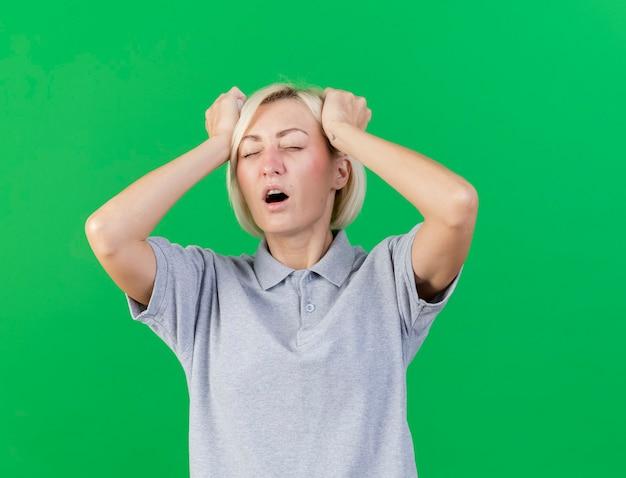 Pijnlijke jonge blonde zieke slavische vrouw legt handen op het hoofd geïsoleerd op groene muur met kopie ruimte