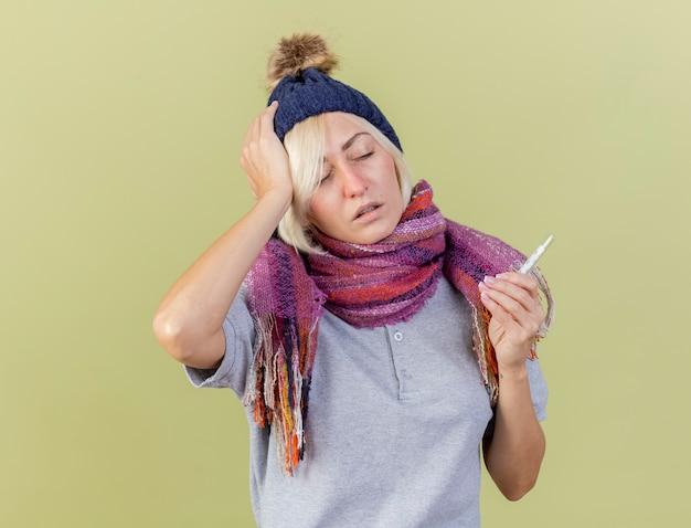 Pijnlijke jonge blonde zieke slavische vrouw met winter muts en sjaal legt hand op het hoofd en houdt thermometer geïsoleerd op olijfgroene muur met kopie ruimte