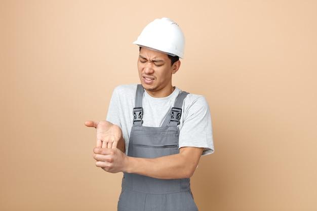 Pijnlijke jonge bouwvakker die veiligheidshelm en uniforme holdingshand met gesloten ogen draagt