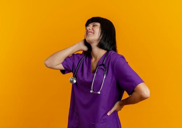Pijnlijke jonge brunette vrouwelijke arts in uniform met een stethoscoop staat zijwaarts met nek achter