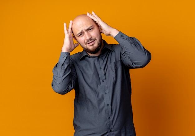 Pijnlijke jonge kale callcentermens die handen op hoofd zet op zoek recht geïsoleerd op oranje met exemplaarruimte
