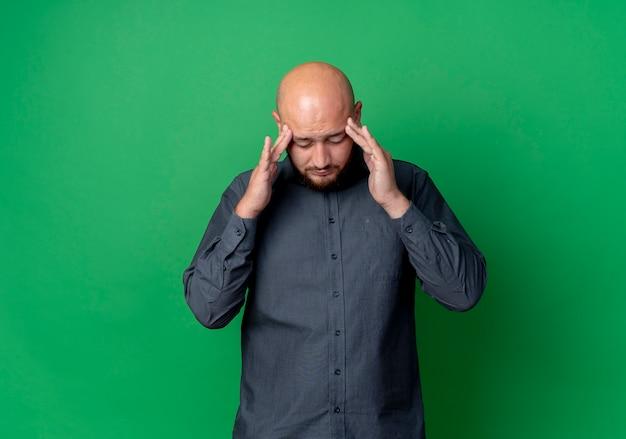 Pijnlijke jonge kale callcentermens die handen op tempels legt die aan hoofdpijn lijden met gesloten ogen die op groen met exemplaarruimte worden geïsoleerd