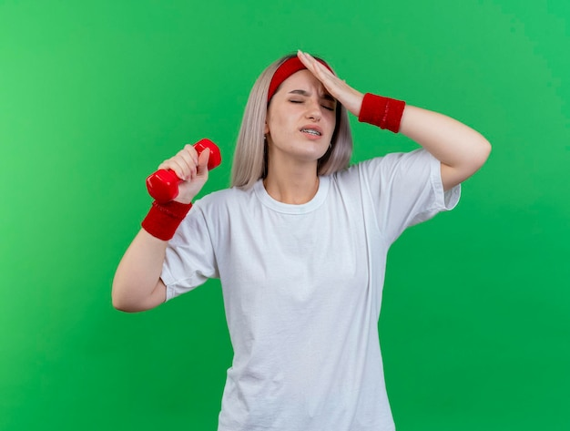 Pijnlijke jonge kaukasische sportieve meisje met beugels dragen hoofdband