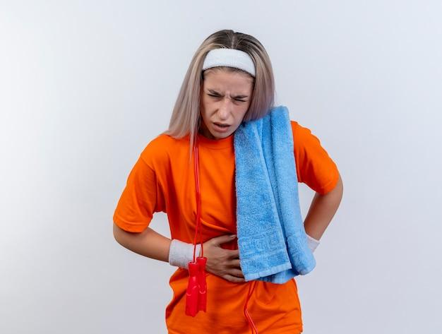 Pijnlijke jonge kaukasische sportieve meisje met beugels en met touwtjespringen om de nek dragen van hoofdband en polsbandjes houden handdoek op schouder legt hand op buik op witte muur