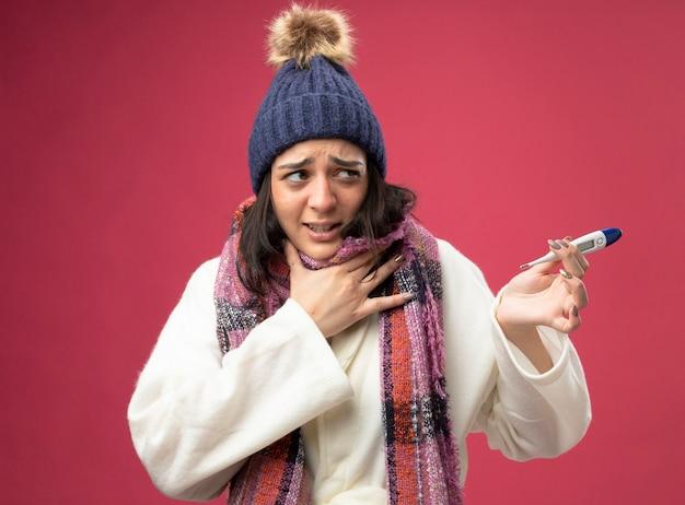Pijnlijke jonge kaukasische ziek meisje draagt gewaad winter muts en sjaal houden thermometer kijken kant zetten hand op keel geïsoleerd op karmozijnrode muur