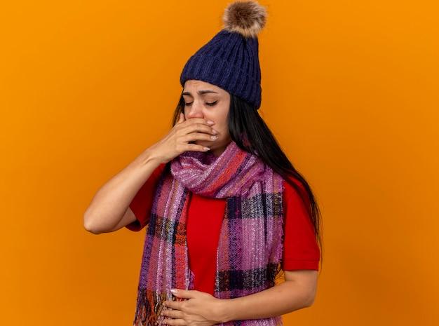 Pijnlijke jonge kaukasische ziek meisje dragen winter hoed en sjaal hand op buik en mond houden klaar om te niezen met gesloten ogen geïsoleerd op oranje muur met kopie ruimte