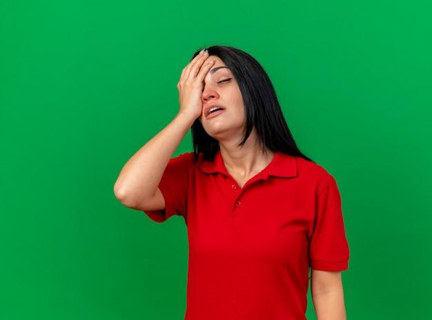 Pijnlijke jonge kaukasische ziek meisje hand op hoofd zetten met gesloten ogen geïsoleerd op groene muur met kopie ruimte