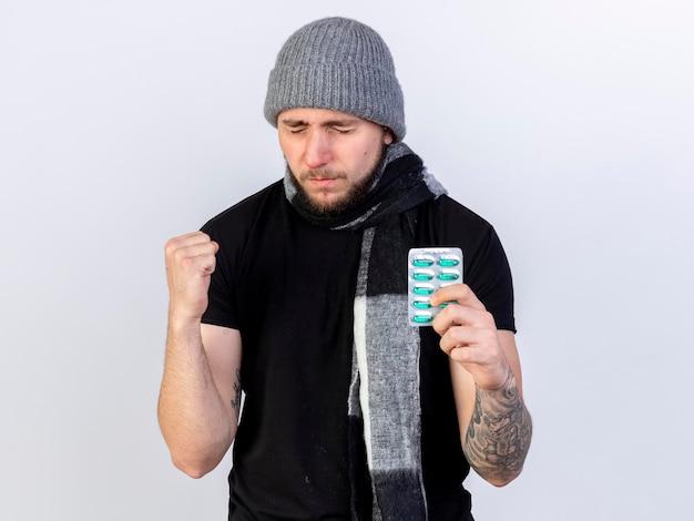 Pijnlijke jonge kaukasische zieke man met winter hoed en sjaal houdt vuist en houdt pakje medische capsules op wit