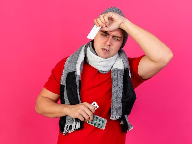 Pijnlijke jonge knappe blonde zieke man met muts en sjaal met verpakkingen van medische pillen naar beneden te kijken en het aanraken van hoofd geïsoleerd op roze muur