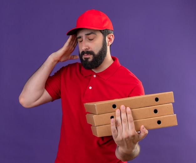 Pijnlijke jonge knappe kaukasische bezorger met rode uniform en pet houden pizzadozen en hand op het hoofd zetten met gesloten ogen die lijden aan hoofdpijn geïsoleerd op paars