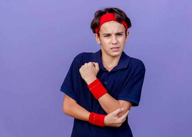Pijnlijke jonge knappe sportieve jongen die hoofdband en polsbandjes met beugels draagt die de elleboog van de zijholding bekijken die op purpere muur wordt geïsoleerd