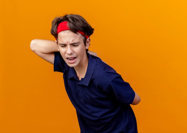 Pijnlijke jonge knappe sportieve jongen die hoofdband en polsbandjes met beugels draagt die de handen achter de rug bij elkaar houden met gesloten ogen geïsoleerd op een oranje muur