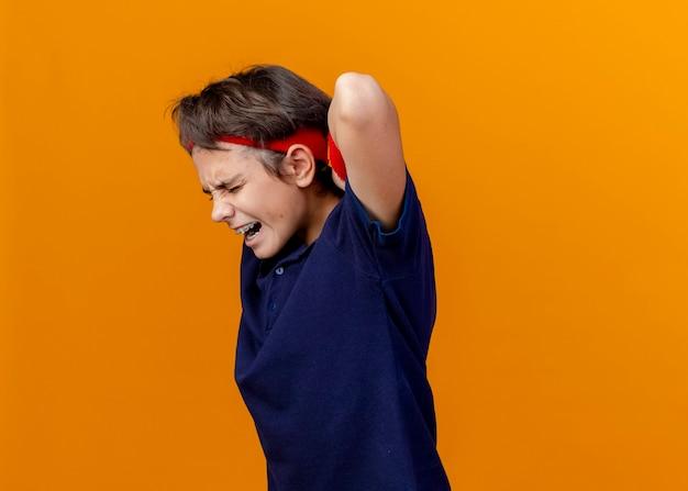 Pijnlijke jonge knappe sportieve jongen die hoofdband en polsbandjes met beugels draagt die zich in profielweergave bevinden die de handen achter de rug houden geïsoleerd op oranje muur