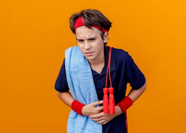 Pijnlijke jonge knappe sportieve jongen met hoofdband en polsbandjes met beugels en handdoek met springtouw op schouders buik vast te houden op zoek recht geïsoleerd op oranje muur