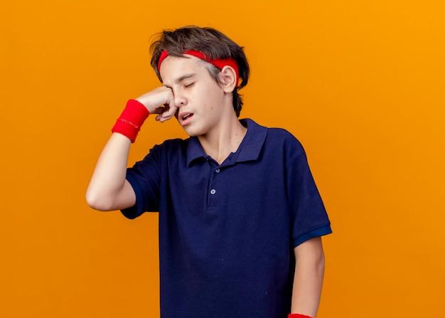 Pijnlijke jonge knappe sportieve jongen met hoofdband en polsbandjes met beugels hand zetten oog met gesloten ogen geïsoleerd op oranje muur met kopie ruimte