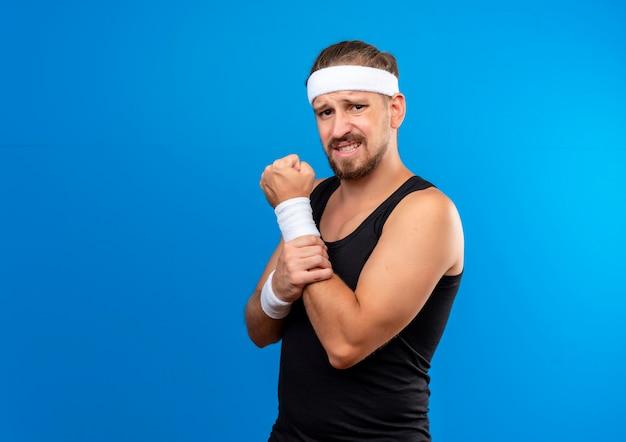 Pijnlijke jonge knappe sportieve man met hoofdband en polsbandjes die de vuist balt en zijn arm geïsoleerd op blauwe muur met kopieerruimte houdt
