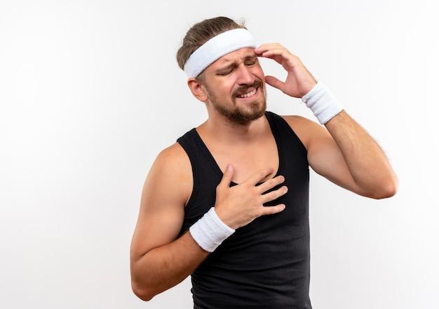 Pijnlijke jonge knappe sportieve man met hoofdband en polsbandjes die handen op tempel en borst zetten met gesloten ogen geïsoleerd op een witte muur met kopieerruimte