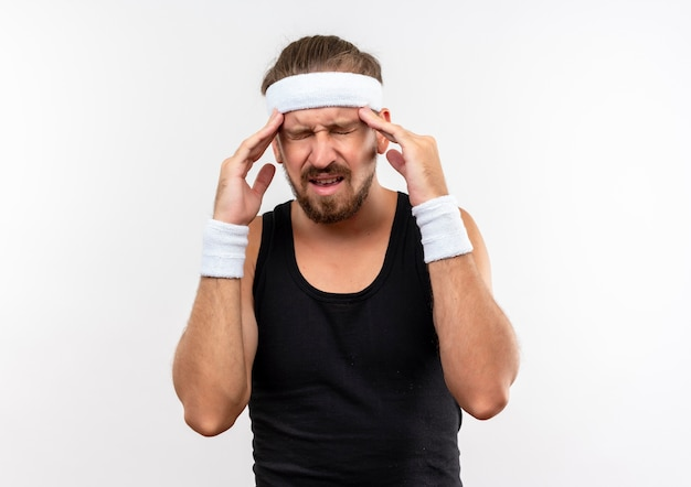 Pijnlijke jonge knappe sportieve man met hoofdband en polsbandjes die handen op tempels zetten die lijden aan hoofdpijn met gesloten ogen geïsoleerd op een witte muur