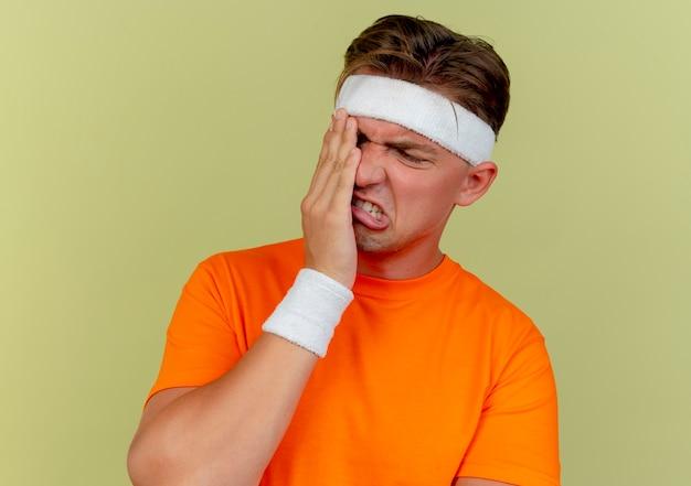 Pijnlijke jonge knappe sportieve man met hoofdband en polsbandjes hand op oog zetten die lijden aan pijn geïsoleerd op olijfgroen