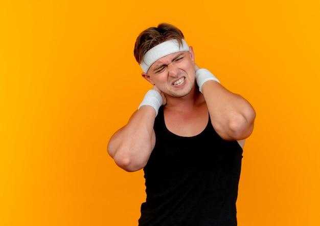 Pijnlijke jonge knappe sportieve man met hoofdband en polsbandjes handen achter nek geïsoleerd op oranje met kopie ruimte