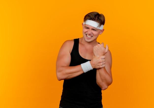 Pijnlijke jonge knappe sportieve man met hoofdband en polsbandjes met pols geïsoleerd op oranje met kopie ruimte