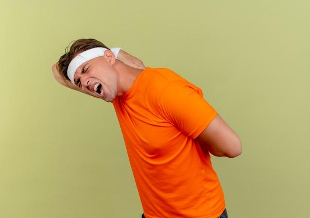 Pijnlijke jonge knappe sportieve man met hoofdband en polsbandjes staande in profielweergave handen op de rug zetten geïsoleerd op olijfgroen