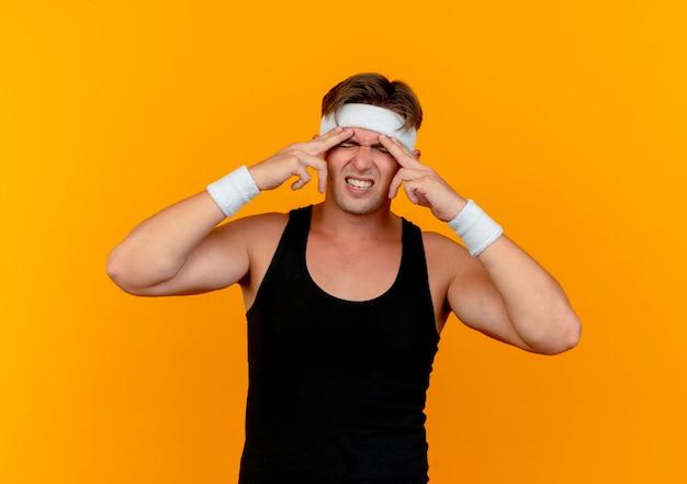 Pijnlijke jonge knappe sportieve man met hoofdband en polsbandjes vingers op voorhoofd lijden hoofdpijn geïsoleerd op oranje