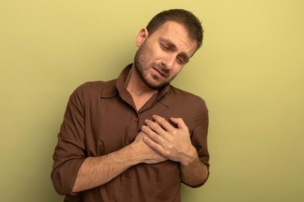 Pijnlijke jonge mens die handen op hart zet neerkijkt geïsoleerd op olijfgroene muur