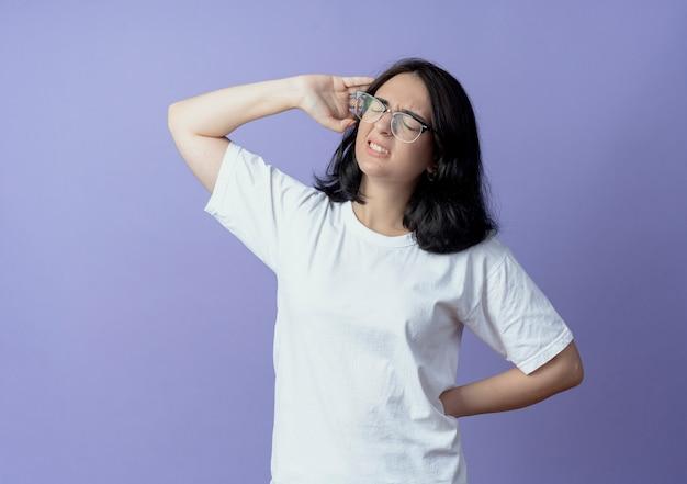 Pijnlijke jonge mooie blanke meisje draagt ?? een bril handen achter de rug en in de buurt van het hoofd met gesloten ogen zetten geïsoleerd op paarse achtergrond met kopie ruimte