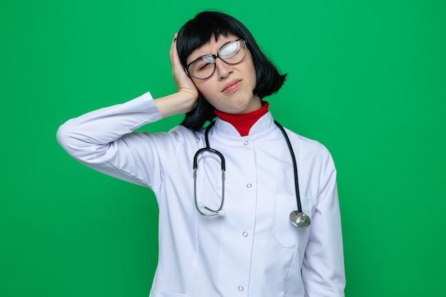 Pijnlijke jonge mooie blanke vrouw met bril in doktersuniform met stethoscoop legt hand op het hoofd
