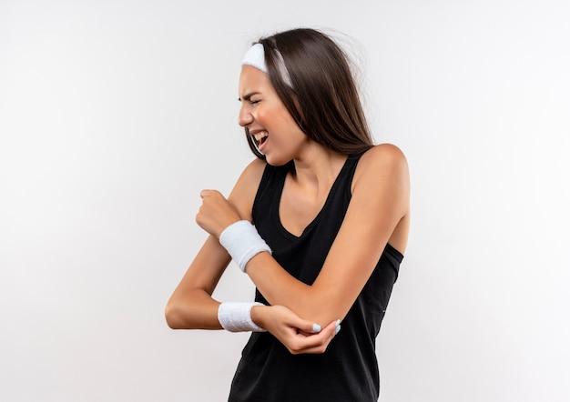 Pijnlijke jonge, mooie sportieve meid met een hoofdband en polsband die de hand op de arm legt met gesloten ogen op een witte muur met kopieerruimte