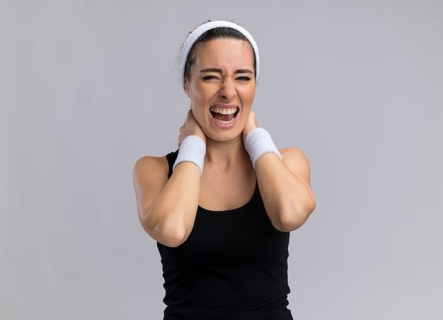 Pijnlijke jonge mooie sportieve vrouw die hoofdband en polsbandjes draagt die de handen in de nek houden