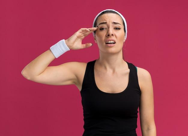 Pijnlijke jonge mooie sportieve vrouw die hoofdband en polsbandjes draagt die het hoofd raken
