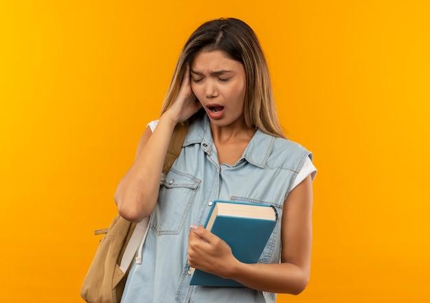 Pijnlijke jonge mooie student meisje dragen rugtas bedrijf boek hand zetten hoofd lijden aan hoofdpijn met gesloten ogen geïsoleerd op oranje met kopie ruimte