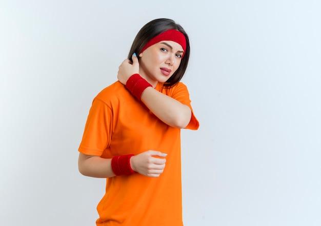 Pijnlijke jonge sportieve vrouw die hoofdband en polsbandjes draagt die het houden hand in lucht aanraken van geïsoleerde hals