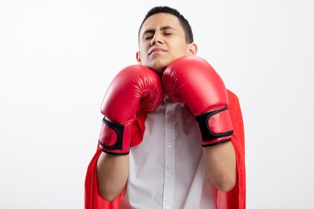 Pijnlijke jonge superheld jongen in rode cape vak handschoenen raken zichzelf in kin met gesloten ogen geïsoleerd op een witte achtergrond met kopie ruimte
