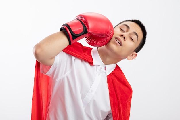 Pijnlijke jonge superheldjongen in rode cape die dooshandschoenen draagt die zich in gezicht met gesloten ogen raken die op witte achtergrond wordt geïsoleerd